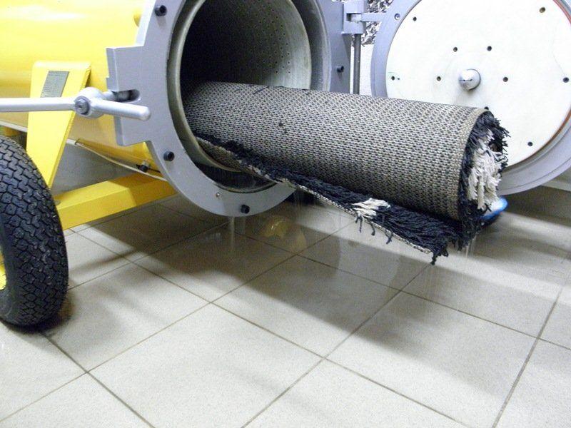 Ubacivanje tepiha u bubanj centrifuge za pranje tepiha